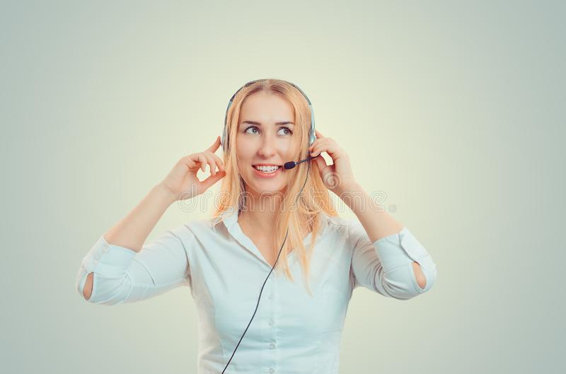 Asian agent woman holding headset looking up smiling happy. stock photo