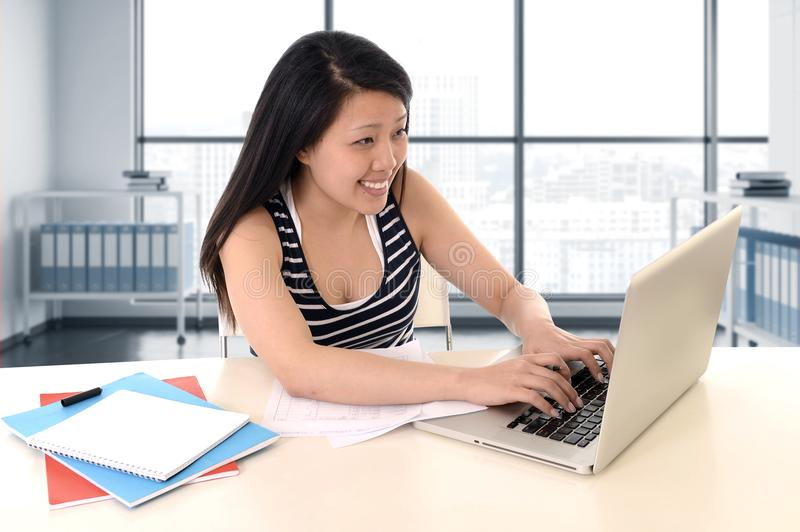 Asian american student working with a smile at modern library office and studying for exam with computer laptop stock photo