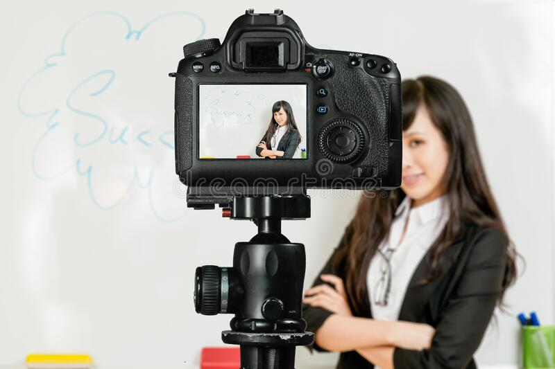 Asian American teacher streaming class with camera royalty free stock images
