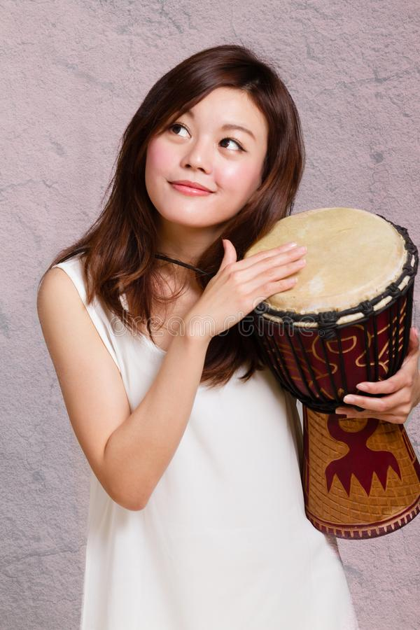 Asian American woman playing African hand drum. Asian American woman playing African djembe hand drum royalty free stock images