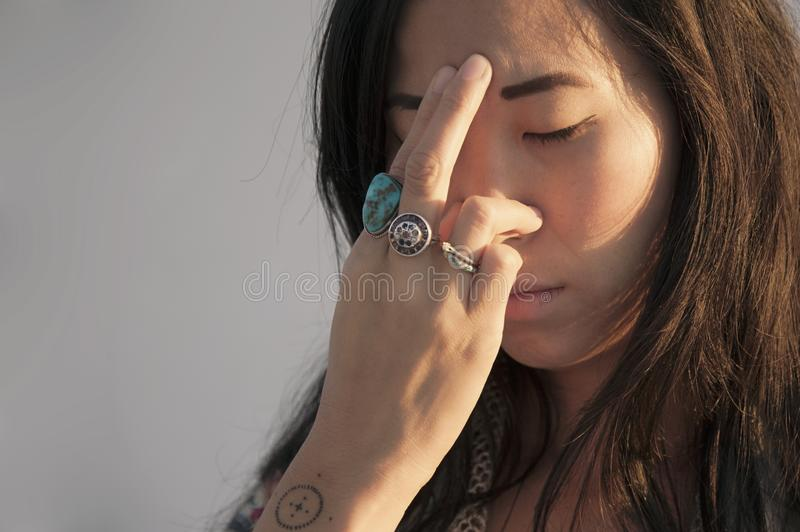 Asian American Woman Practicing Pranayama. Portrait of an asian american woman photographed on a white background practicing pranayama or breathwork. This stock images