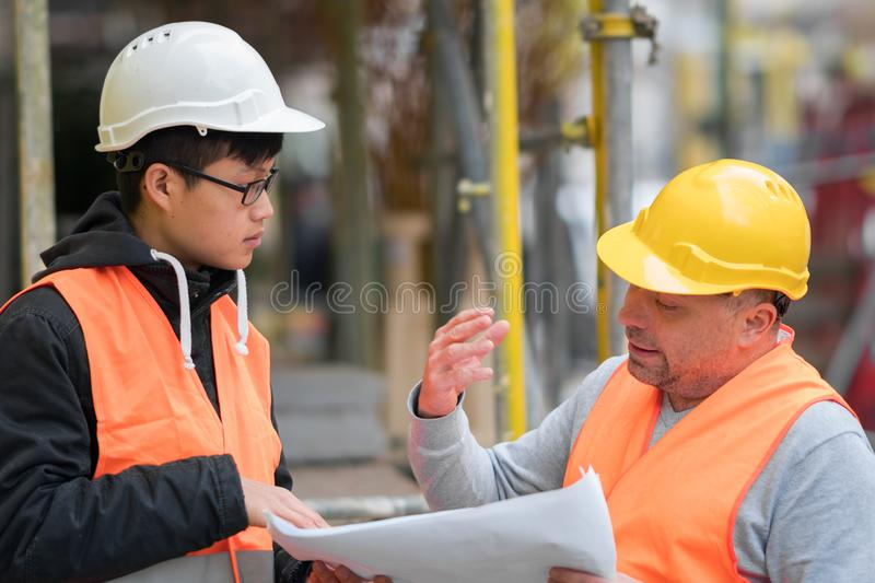 Asian apprentice engineer at work on construction site with the senior manager. Young Asian trainee engineer at work on construction site with the senior manager royalty free stock photos