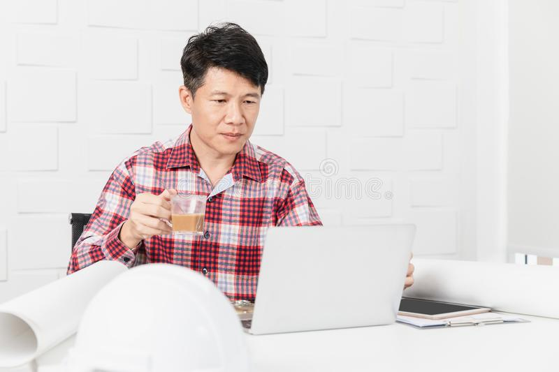 Asian architect at construction site office. Middle aged Asian architect, in checked shirt, working at construction site office, relax with morning coffee stock image
