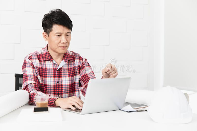 Asian architect at construction site office. Middle aged Asian handsome architect, in checked shirt, working at construction site office, busy on making building stock image