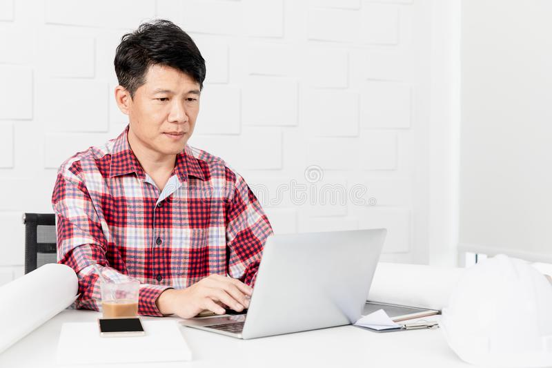 Asian architect at construction site office. Middle aged Asian handsome architect, in checked shirt, working at construction site office, busy on making building royalty free stock photography