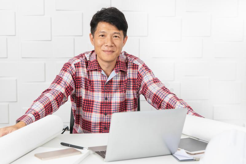 Asian architect at construction site office. Middle aged Asian handsome architect, in checked shirt, working at construction site office and documents in stock photography