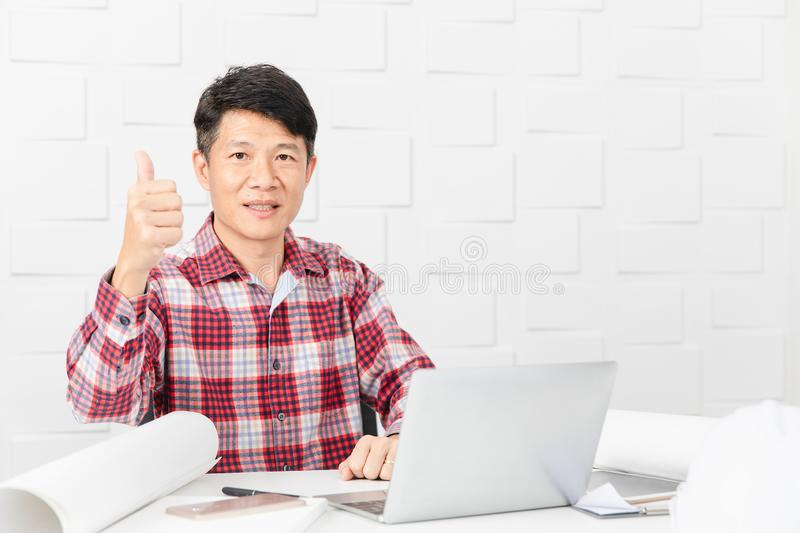 Asian architect at construction site office. Middle aged Asian handsome architect, in checked shirt, working at construction site office, making thumb up gesture stock image
