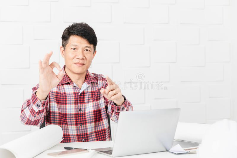 Asian architect at construction site office. Middle aged Asian handsome architect, in checked shirt, working at construction site office, talking on smartphone royalty free stock photo