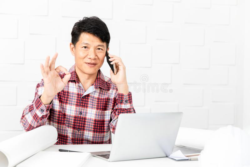 Asian architect at construction site office. Middle aged Asian handsome architect, in checked shirt, working at construction site office, talking on smartphone royalty free stock photography