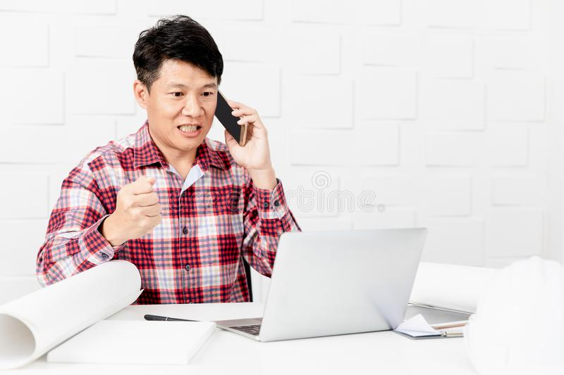 Asian architect at construction site office. Middle aged Asian handsome architect, in checked shirt, working at construction site office, talking to executive royalty free stock image