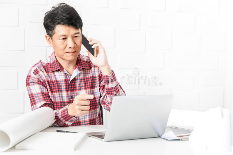 Asian architect at construction site office. Middle aged Asian handsome architect, in checked shirt, working at construction site office, talking to executive royalty free stock photos