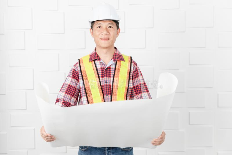 Asian architect at construction site office. Middle aged Asian handsome architect, in jeans and checked shirt, wearing orange, yellow reflective safety vest, and royalty free stock images