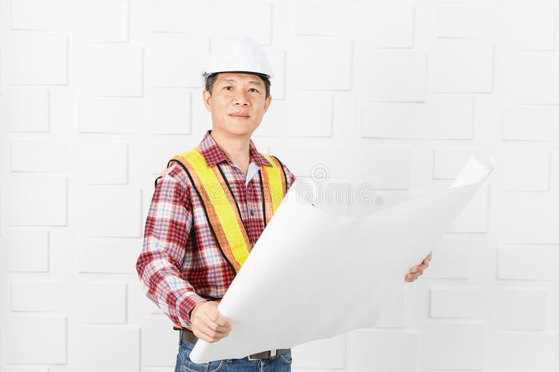 Asian architect at construction site office. Middle aged Asian handsome architect, in jeans and checked shirt, wearing orange, yellow reflective safety vest, and royalty free stock photos