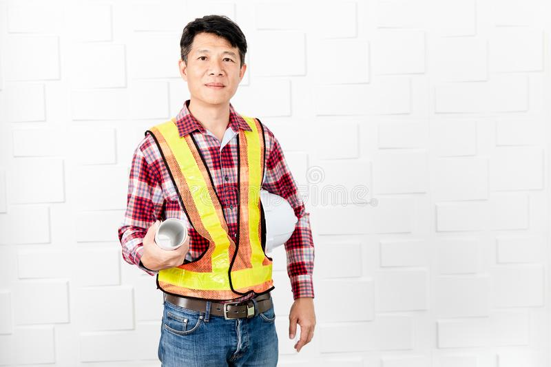 Asian architect at construction site office. Middle aged Asian handsome architect, in jeans and checked shirt, wearing orange, yellow reflective safety vest royalty free stock photo