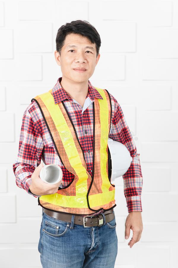 Asian architect at construction site office. Middle aged Asian handsome architect, in jeans and checked shirt, wearing orange, yellow reflective safety vest royalty free stock image