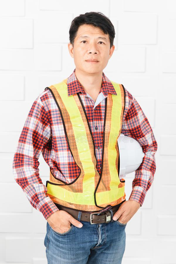 Asian architect at construction site office. Middle aged Asian handsome architect, in jeans and checked shirt, wearing orange, yellow reflective safety vest royalty free stock photography