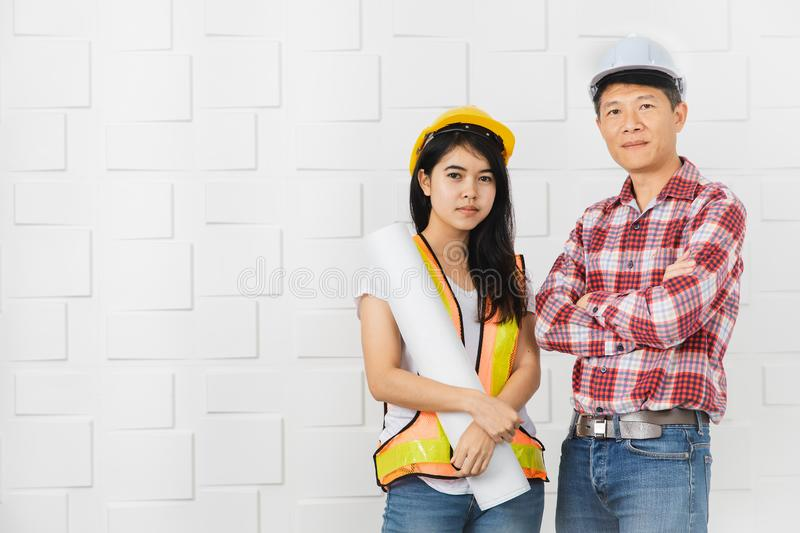 Asian architect at construction site office. Middle aged Asian architect, in jeans and checked shirt, cross her arm young female Asian assistant, wearing orange royalty free stock images