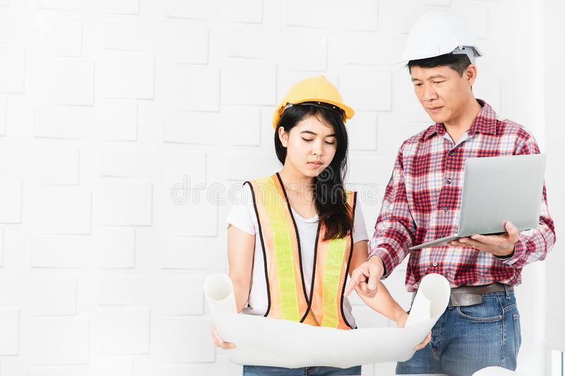 Asian architect at construction site office. Middle aged Asian architect, in jeans and checked shirt, showing data on laptop to young female Asian assistant stock images