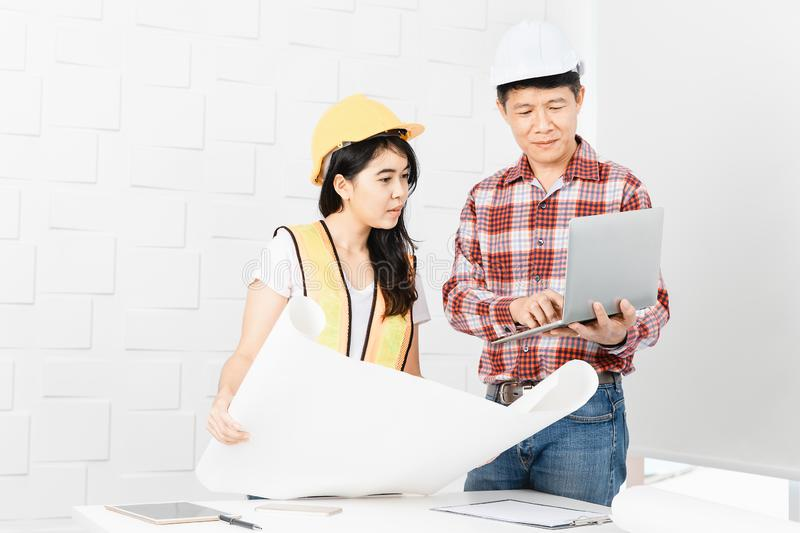 Asian architect at construction site office. Middle aged Asian architect, in jeans and checked shirt, showing data on laptop to young female Asian assistant stock photo
