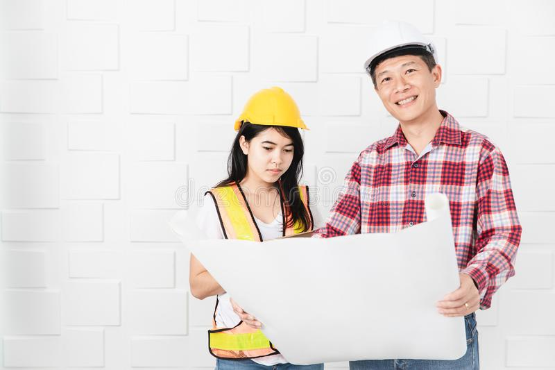 Asian architect at construction site office. Middle aged Asian architect, in jeans and checked shirt, wearing hardhat, teaching his young female Asian assistant stock photos