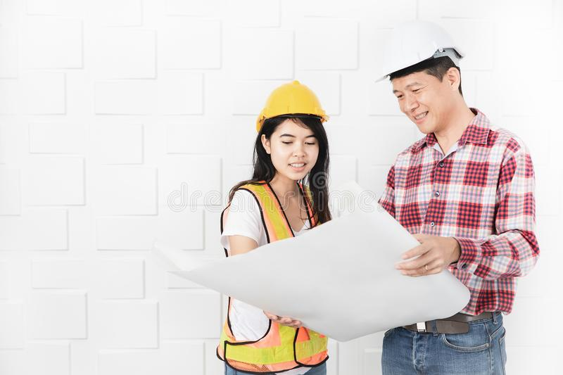 Asian architect at construction site office. Middle aged Asian architect, in jeans and checked shirt, wearing hardhat, teaching his young female Asian assistant royalty free stock photography