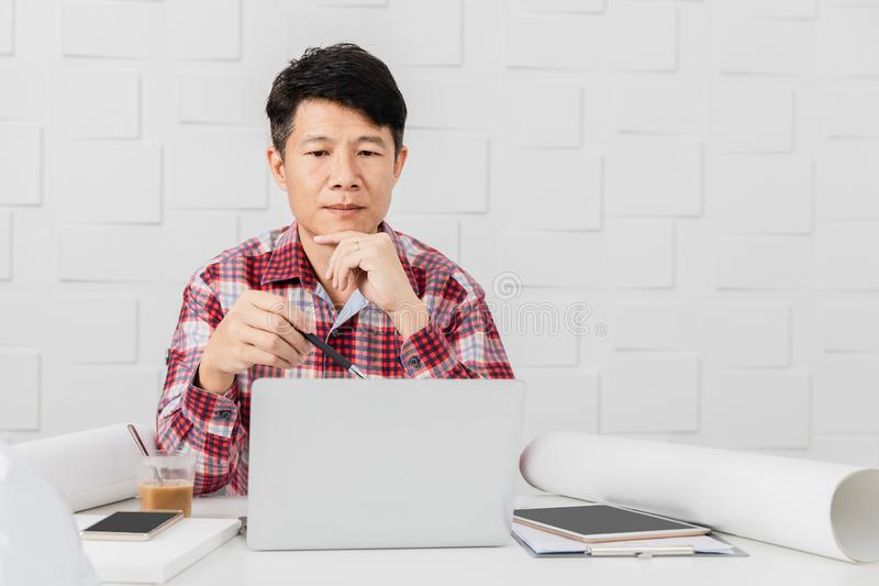Asian architect at construction site office. Portrait of middle aged Asian handsome architect, in checked shirt, working at construction site office, busy on stock image
