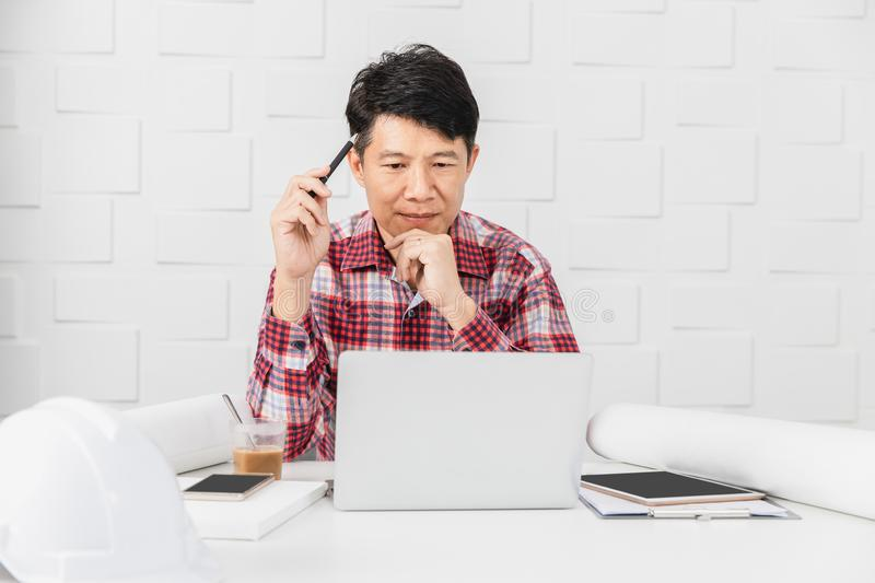 Asian architect at construction site office. Portrait of middle aged Asian handsome architect, in checked shirt, working at construction site office, busy on royalty free stock photography