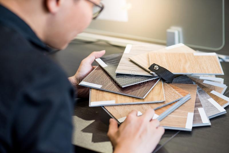 Asian architect man choosing wooden color swatch stock image