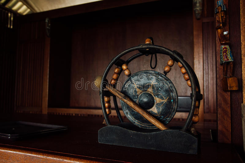 Asian authentic gong. Ancient percussion instrument gong. Asian gong drum black on a dark wood background stock image