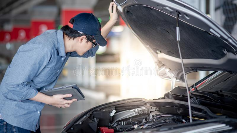 Asian auto mechanic checking the car using tablet stock photo