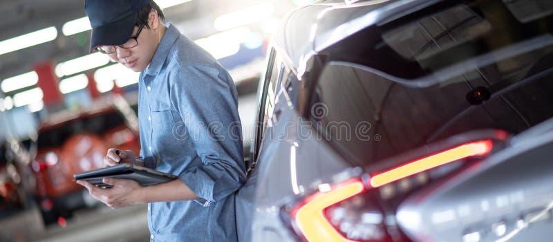 Asian auto mechanic checking the car using tablet. Young Asian auto mechanic holding digital tablet checking car in auto service garage. Mechanical maintenance royalty free stock photo