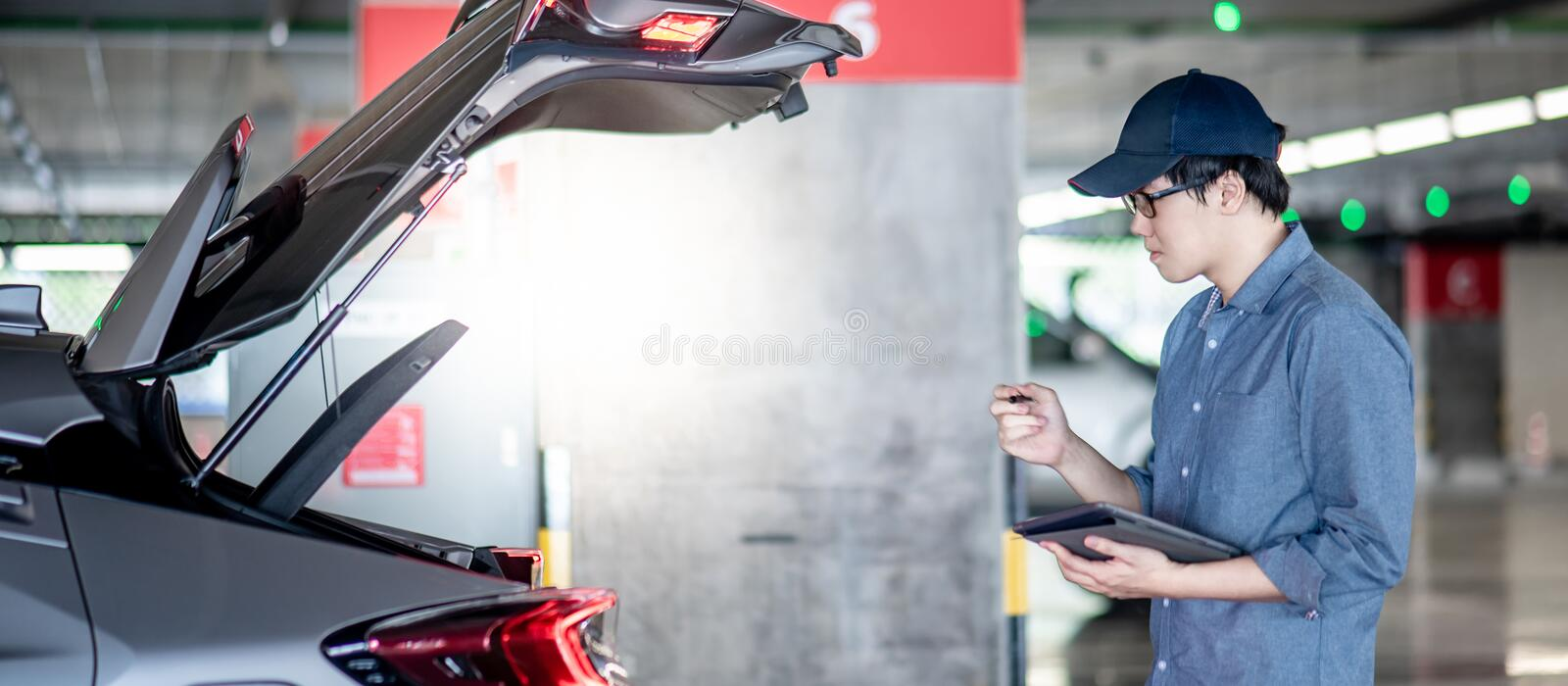 Asian auto mechanic checking the car using tablet. Young Asian auto mechanic holding digital tablet checking tailgate in auto service garage. Mechanical royalty free stock photos
