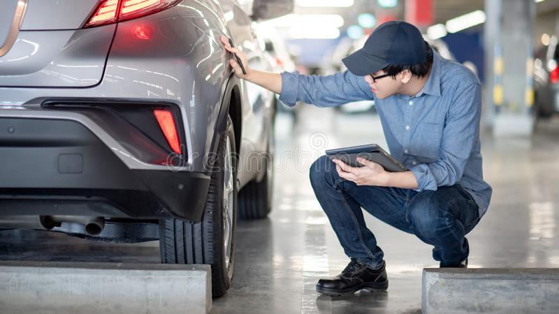 Asian auto mechanic checking the car using tablet. Young Asian auto mechanic holding digital tablet checking car wheel in auto service garage. Mechanical stock images