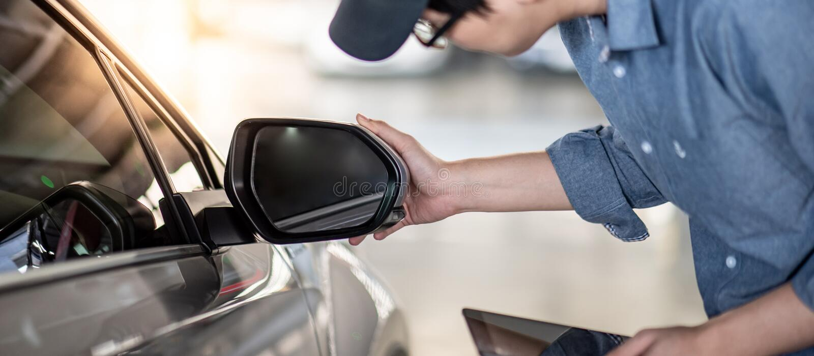 Asian auto mechanic checking car wing mirror. Young Asian auto mechanic holding digital tablet checking car wing mirror. Mechanical maintenance engineer working royalty free stock photography