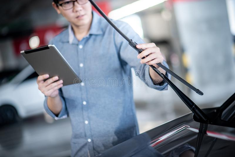 Asian auto mechanic checking windshield wiper. Young Asian auto mechanic holding digital tablet checking windshield wiper in auto service garage. Mechanical stock image