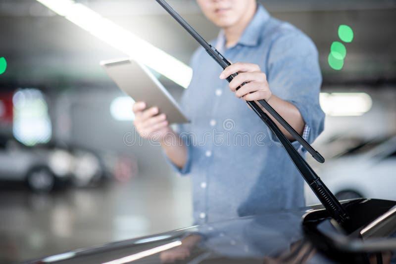 Asian auto mechanic checking windshield wiper stock photo