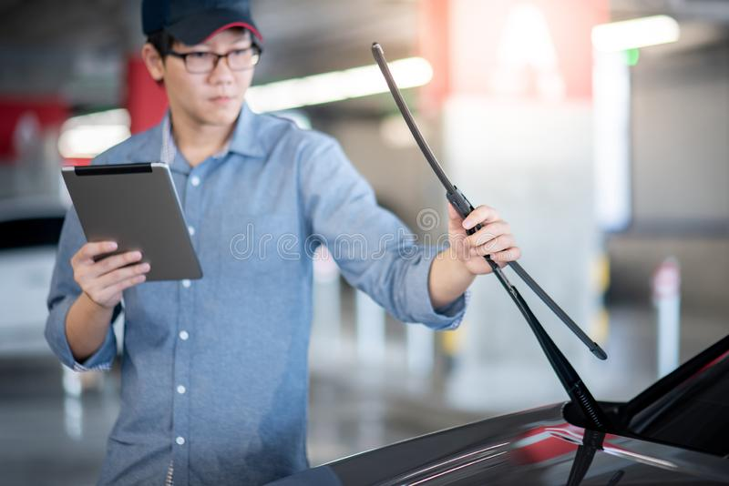 Asian auto mechanic checking windshield wiper. Young Asian auto mechanic holding digital tablet checking windshield wiper in auto service garage. Mechanical royalty free stock photography