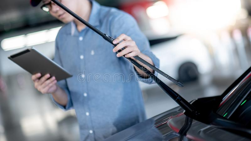 Asian auto mechanic checking windshield wiper. Young Asian auto mechanic holding digital tablet checking windshield wiper in auto service garage. Mechanical royalty free stock image