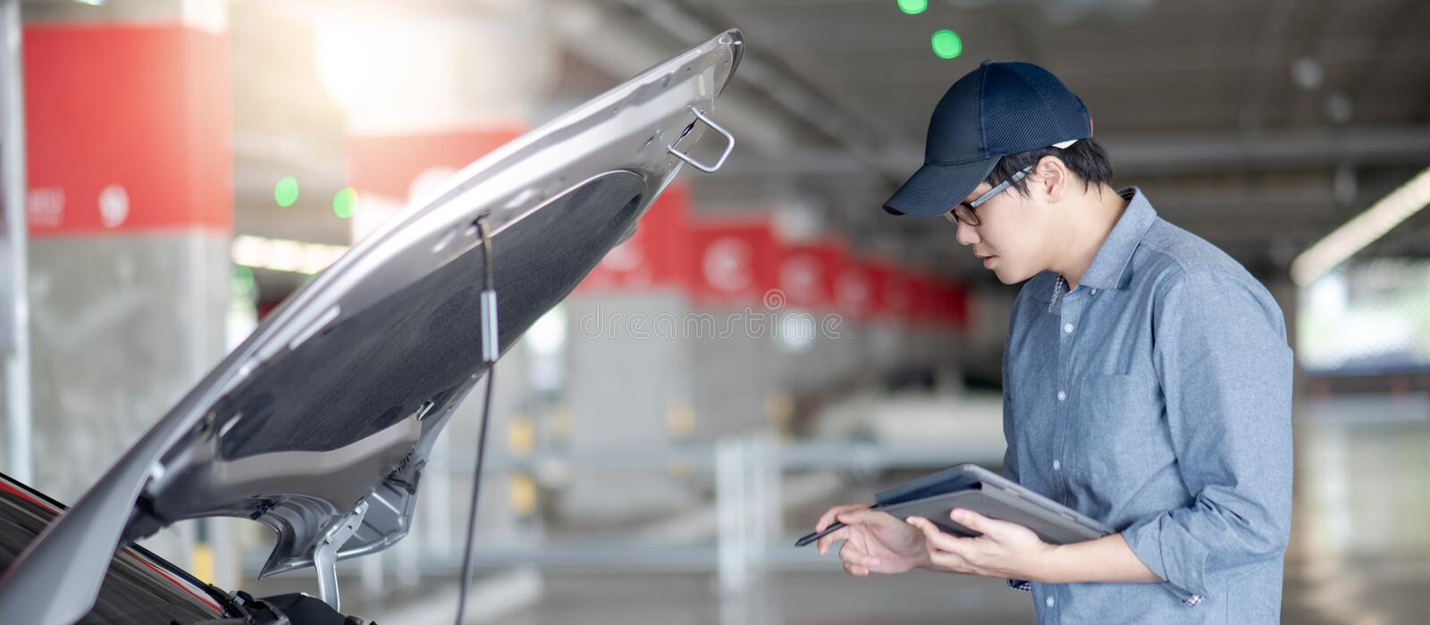 Asian auto mechanic checking the car using tablet. Asian auto mechanic holding digital tablet checking car engine under the hood in auto service garage stock photos