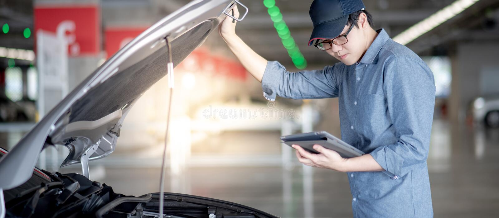 Asian auto mechanic checking the car using tablet. Asian auto mechanic holding digital tablet checking car engine under the hood in auto service garage royalty free stock photos