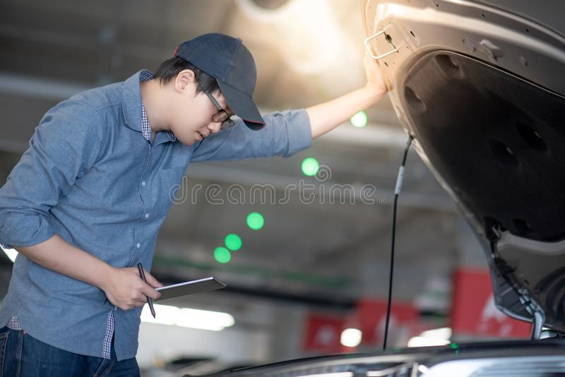 Asian auto mechanic checking the car using tablet. Asian auto mechanic holding digital tablet checking car engine under the hood in auto service garage royalty free stock images