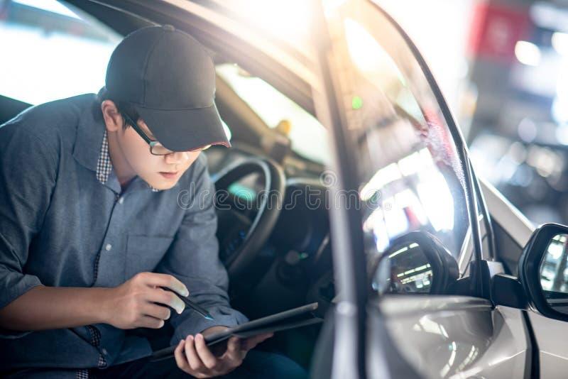 Asian auto mechanic checking the car using tablet. Asian auto mechanic sitting on driver seat checking the car using digital tablet in auto service garage stock photography