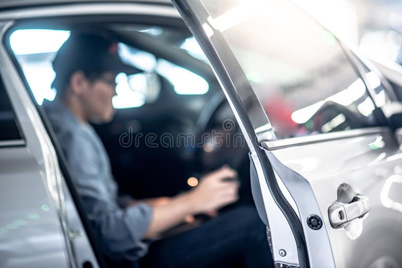 Asian auto mechanic sitting inside of the car stock image