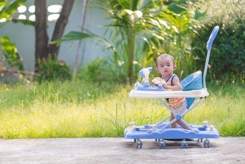 Asian baby in the baby walker. Asian cute baby in the baby walker, plants background stock photography