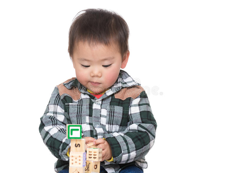 Asian baby boy concentrate on playing toy block. Isolated on white royalty free stock image
