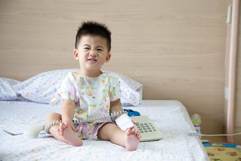 Asian baby boy smiling and wear patients suits sitting on bed in the room at child department in the hospital. stock photography