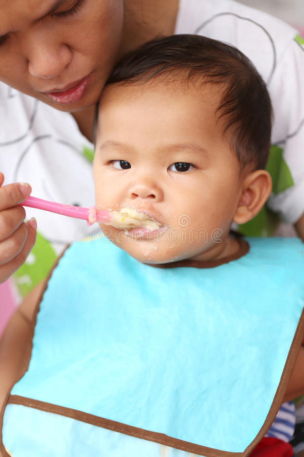 Asian baby boy to eating food in concept of health foods and nut. Rition for development and growth royalty free stock images