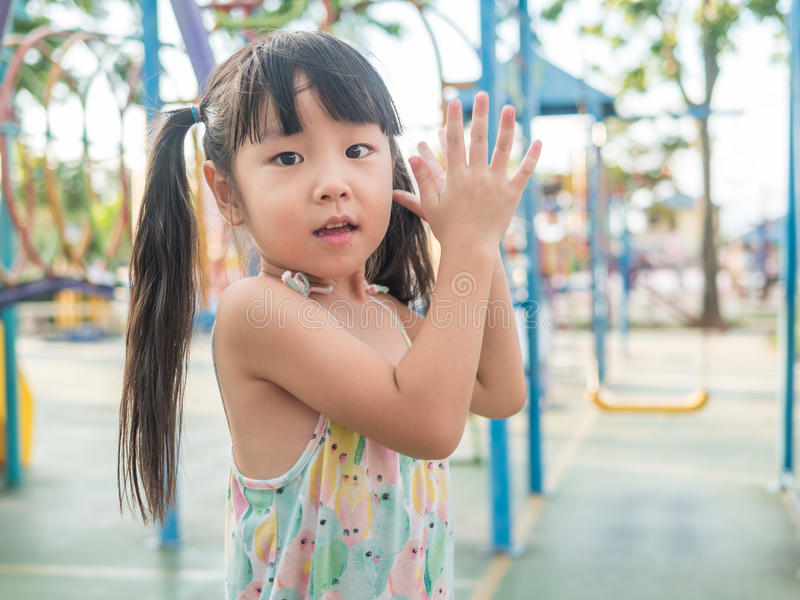 Asian baby child playing on playground. Clap her hands action royalty free stock image