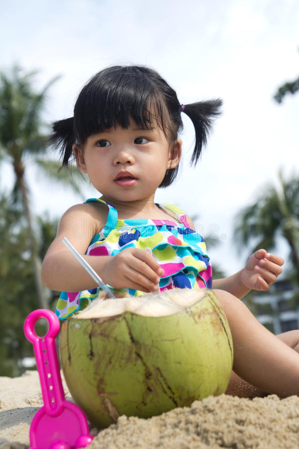 Asian baby girl on beach. Asian baby girl with coconut fruit on beach royalty free stock images