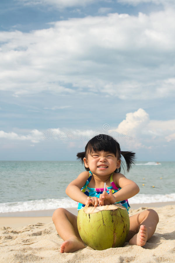Asian baby girl on beach. Asian baby girl with coconut fruit on beach stock images